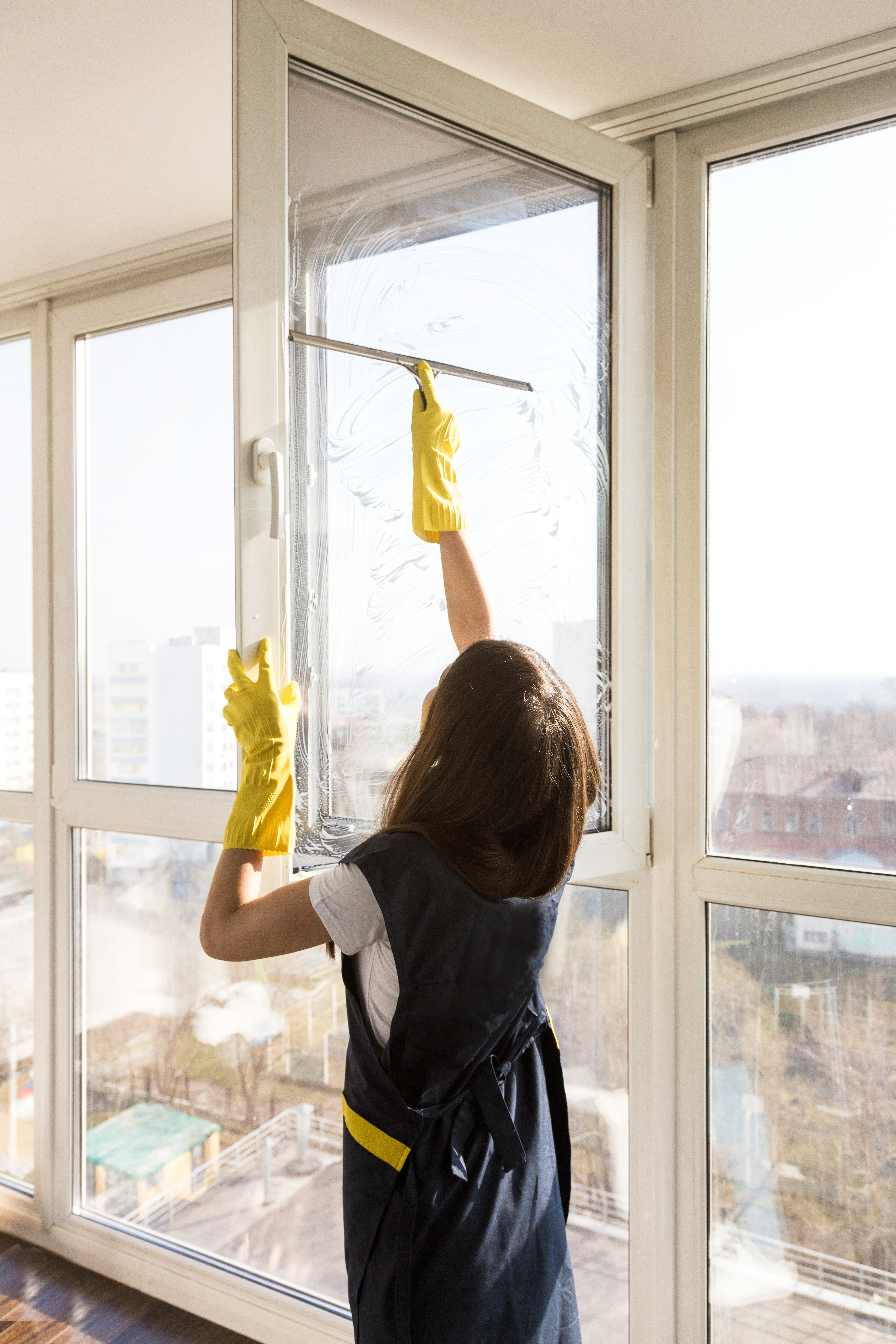 Close-up of a woman in uniform and yellow gloves washes a windows with window scraper. Professional home cleaning.