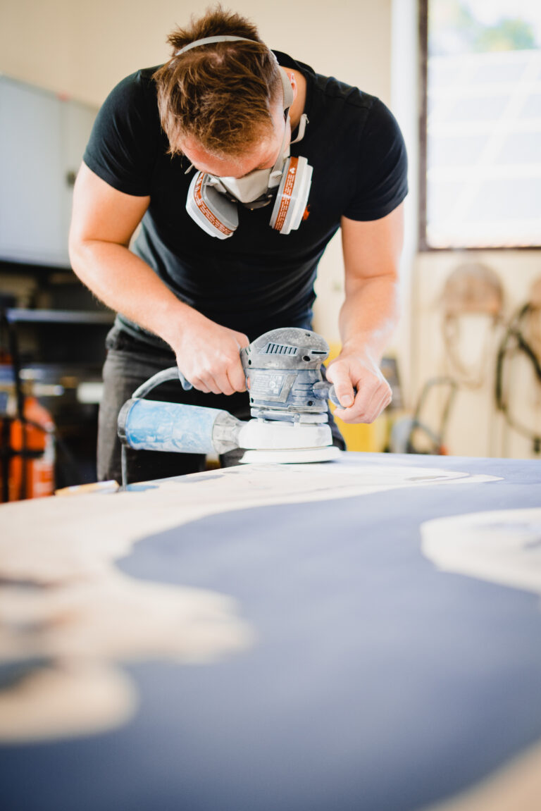 Woodworker using orbtail sander with epoxy table