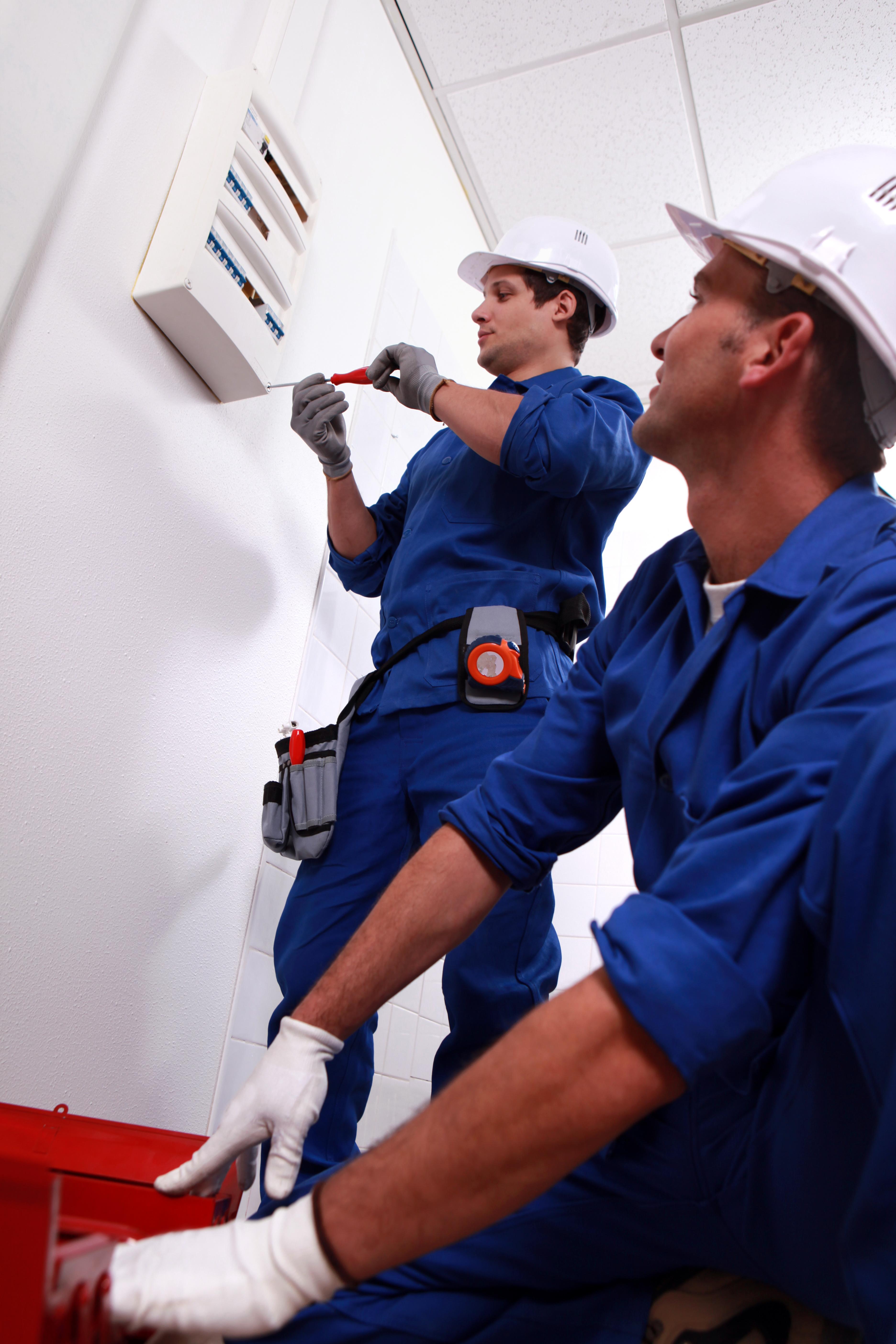 Electricians installing circuit breaker