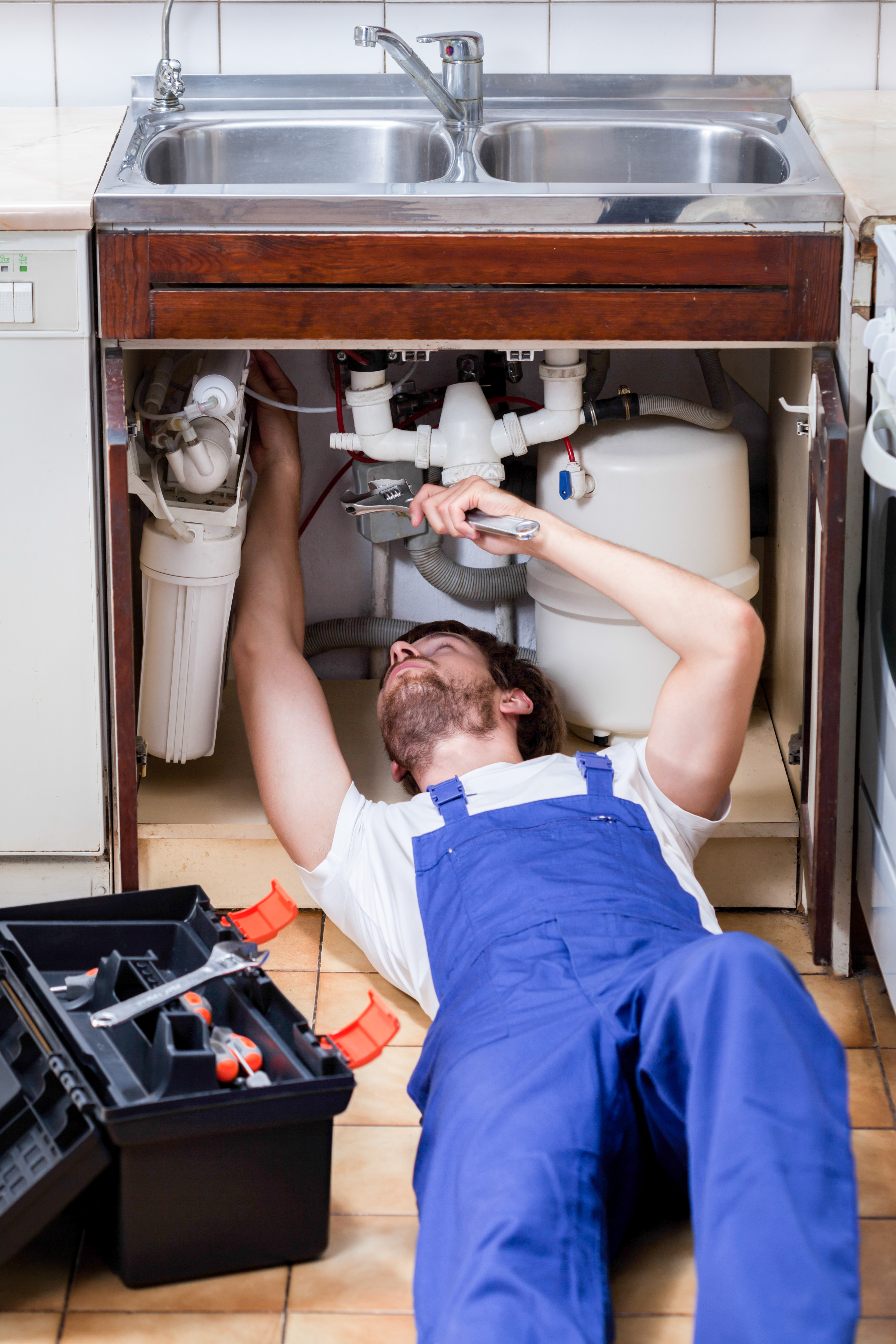 A handyman lying on the floor with a tool box fixing sink