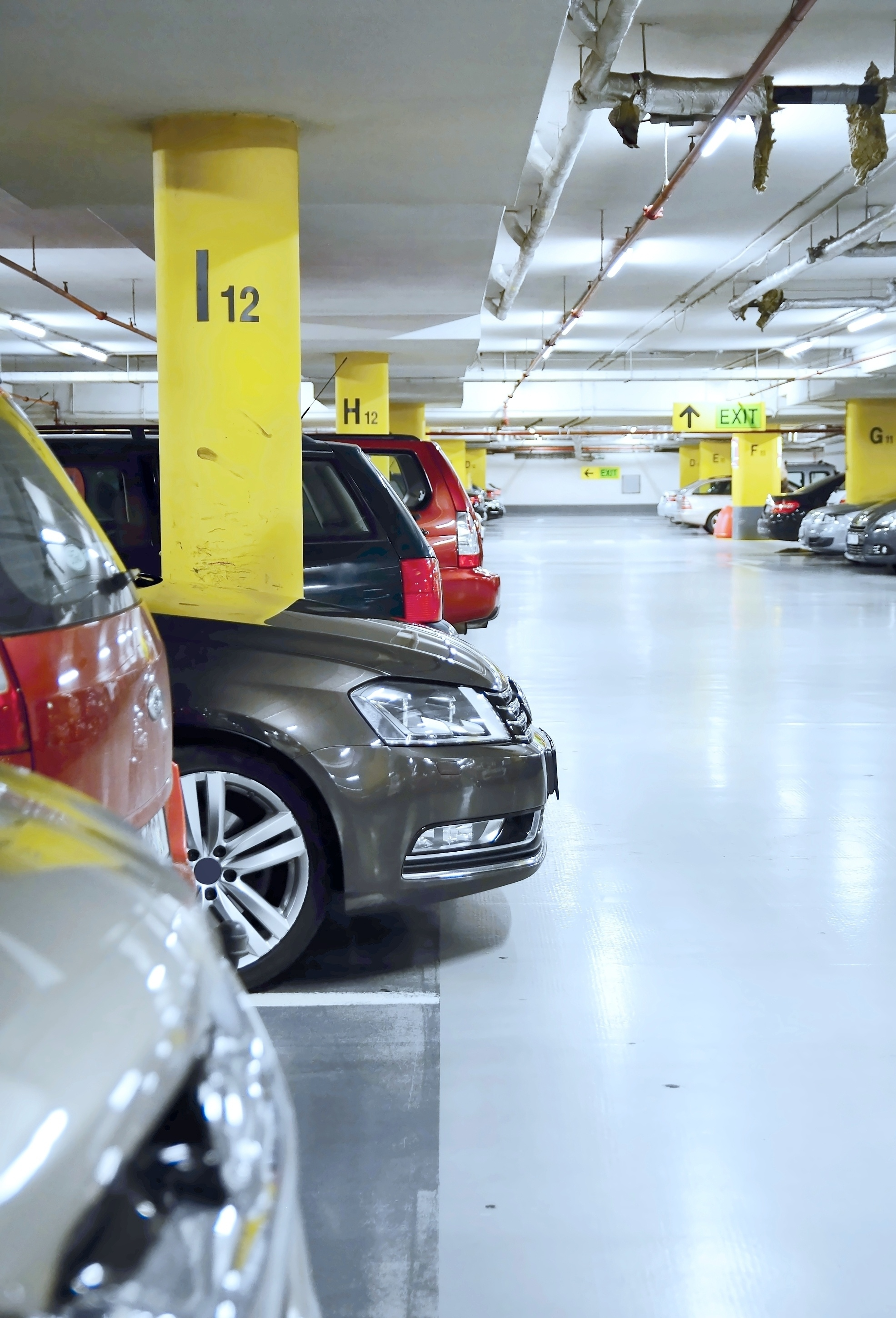 Underground parking garage at shopping center with parked cars.