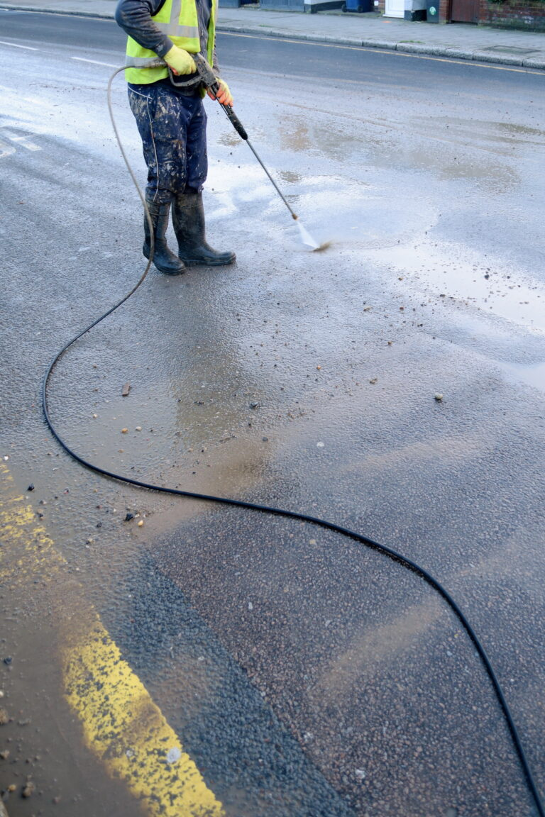 Construction worker cleaning street with water hose