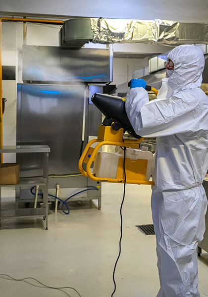 man in protective equipment disinfects with a spray gun industrial kitchen surfaces due to coronavirus covid-19 .Virus pandemic